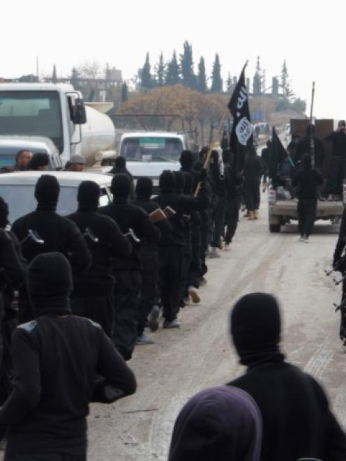 Fighters of al-Qaeda linked Islamic State of Iraq and the Levant parade at the Syrian town of Tel...