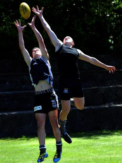 Fighting for the ball at Littlebourne yesterday are Otago Boys' High School pupils Chris McNoe ...