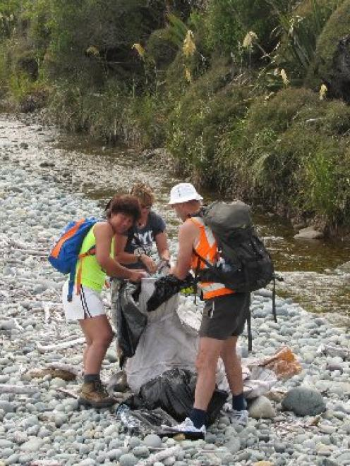 Filling a fadge with rubbish between Barn Bay and Sandrock Bluff are (from left) Marietta Gibb,...