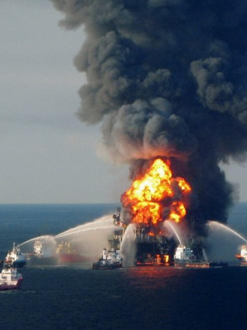 Fire crews battle the blazing remnants of the offshore oil rig Deepwater Horizon, off Louisiana,...
