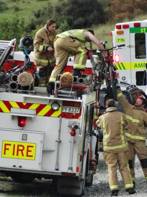Fire volunteers take care of mountain bikes after a crash on Moke Lake Rd, near Queenstown, left...