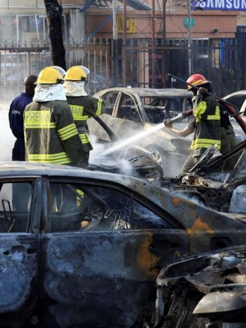 Firefighters douse cars after a bomb blast at a crowded shopping district in Abuja. REUTERS...