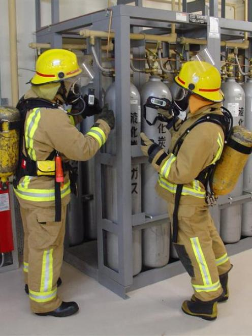 Firefighters Kris Robb (left) and Karen Brown use a gas detector to check CO2 and oxygen levels...