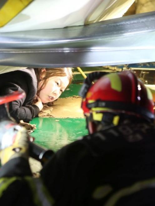 Firefighters try to rescue a student trapped by debris from the collapsed building. REUTERS/Lee...