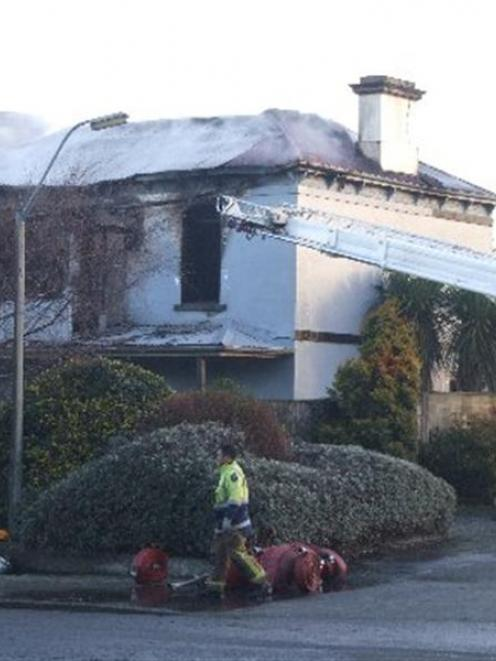 Firefighters work on the remains of the Road Knights' Invercargill headquarters destroyed in a...