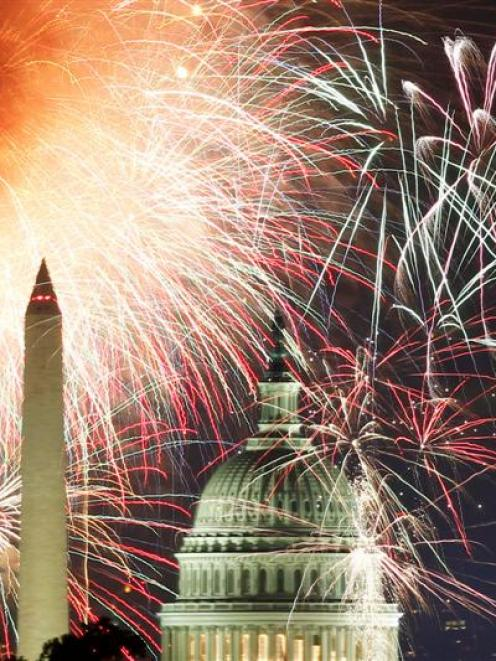 Fireworks light up the sky over the United States Capitol dome and the Washington Monument as the...