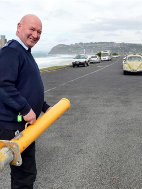 First Security operations manager Garry McLennan removes bollards at the St Kilda end of the road...