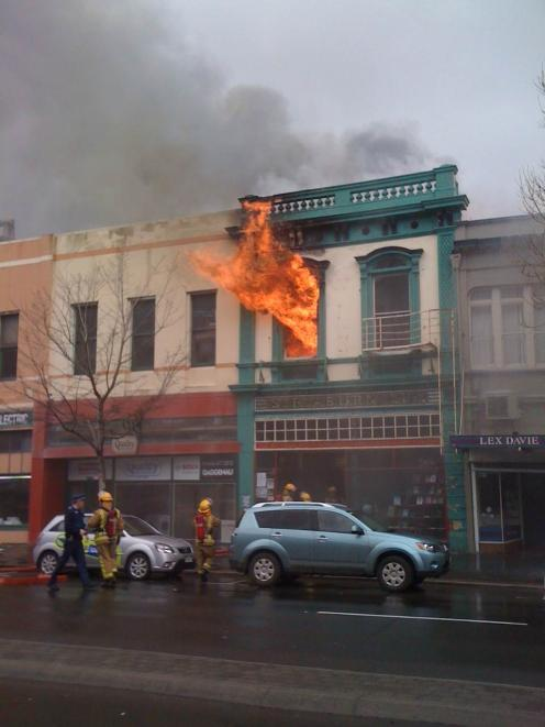 Flames shoot out of the building at 2.30pm. Photo by Craig Baxter