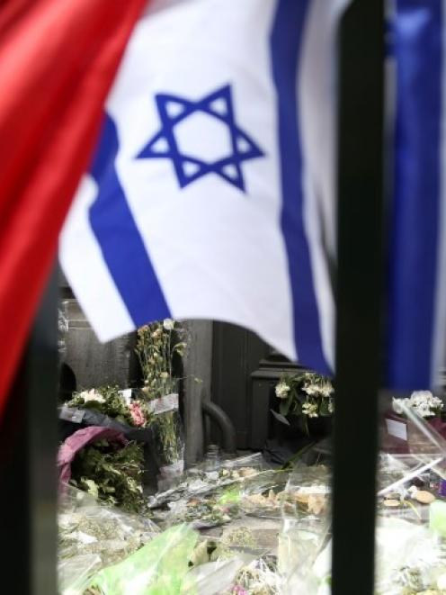 Flowers are seen near an Israeli flag at the entrance of the Jewish Museum in Brussels. REUTERS...