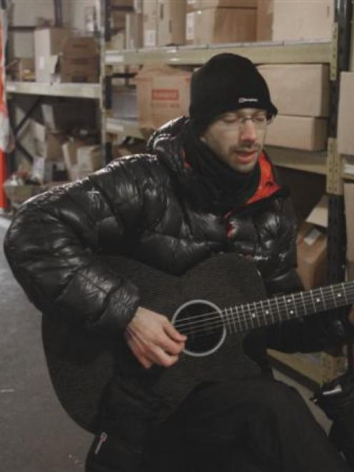 Folk musician Jake Wilson practises in a commercial chiller for his gig on the ice. Photo supplied.