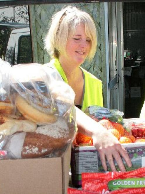 FoodShare volunteer Kate Springford (left) and driver Desi Liversage unload a van  of donated...