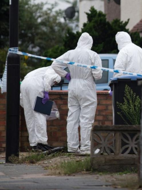 Forensic investigators examine the London property where the woman was reportedly beheaded. ...