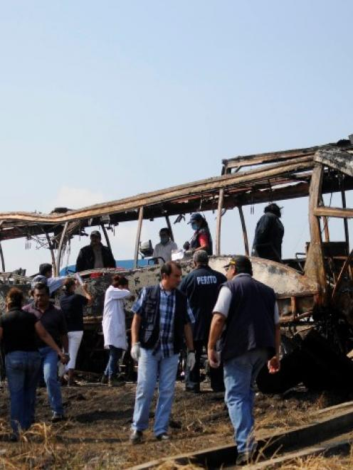 Forensic staff and red cross members inspect the remains of the bus. REUTERS/Angel Hernandez