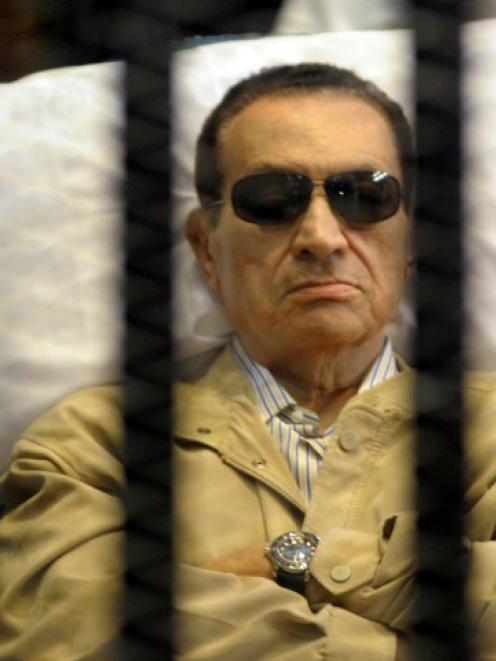 Former Egyptian president Hosni Mubarak sits inside a cage in a courtroom in Cairo in this June...