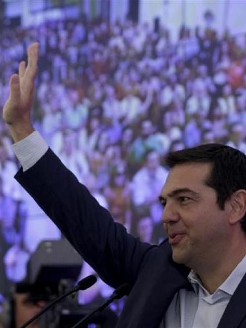 Former Greek Prime Minister Alexis Tsipras waves during a meeting with members of his Syriza...