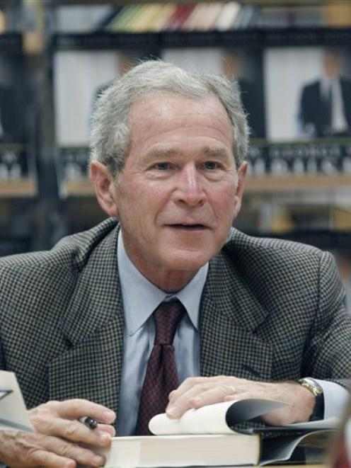 Former President George W. Bush signs a copy of his book 'Decision Points' at a store near his...