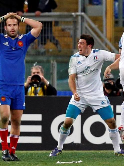 France's Frederic Michalak looks on as Italy's players celebrate at the end of the match in their...