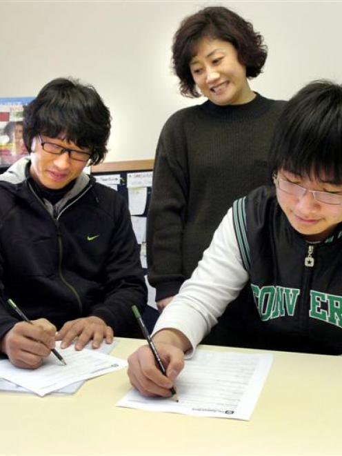 Francesca Shin assists Korean students Lee Deokjae (25), left, and Nick Yu (15) with opening bank...