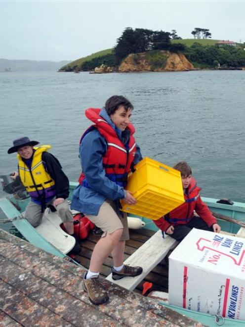 Francine Vella loads the boat, as her husband Alex King and son George Vella-King (13) look on,...