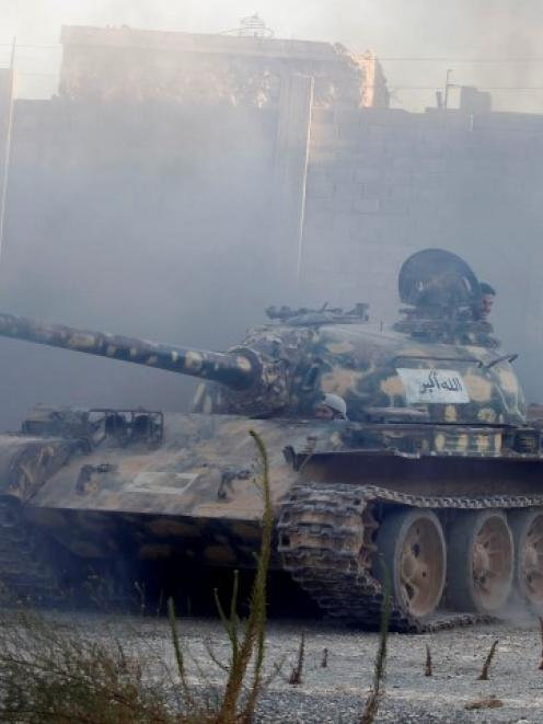 Free Syrian Army fighters drive a tank towards the front line in Aleppo's Sheikh Saeed...