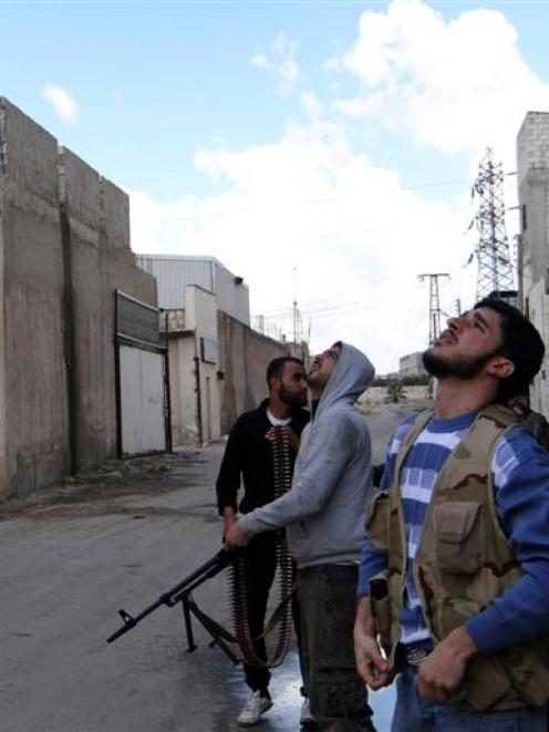 Free Syrian Army fighters look at an overhead jet during clashes with forces loyal to Syria's...