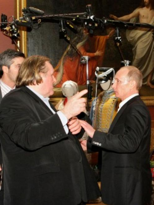 French actor Gerard Depardieu (L) speaks with Vladimir Putin, then Russian Prime Minister, during...