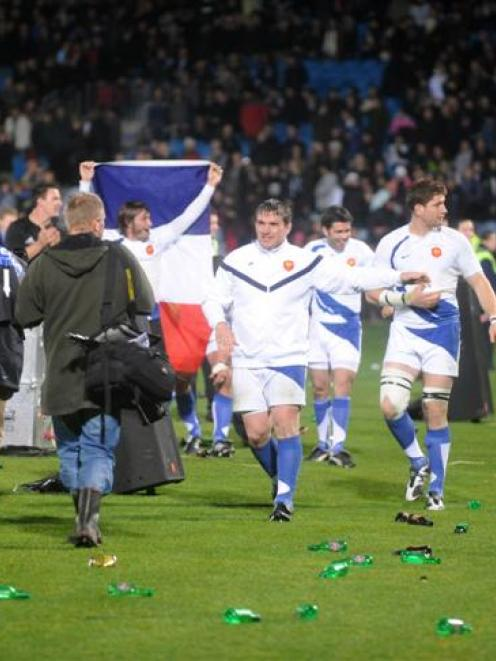 French players walk over a part of Carisbrook littered with bottles after Saturday night's test...