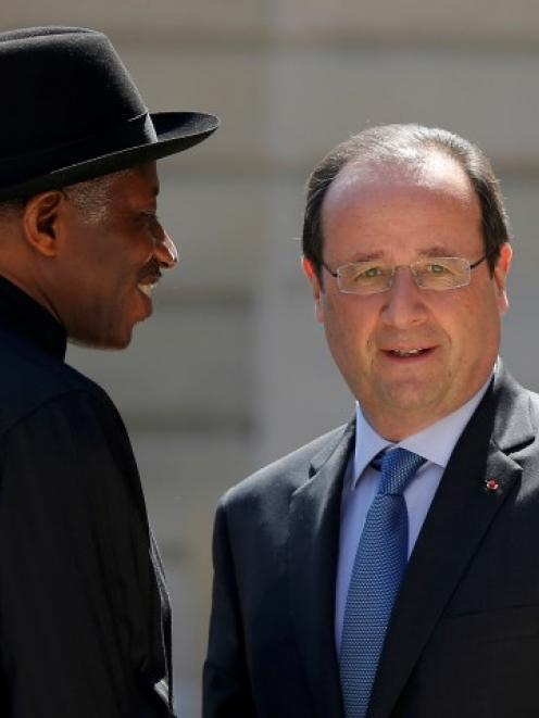 French President Francois Hollande (R) welcomes Nigerian President Goodluck Jonathan as he...