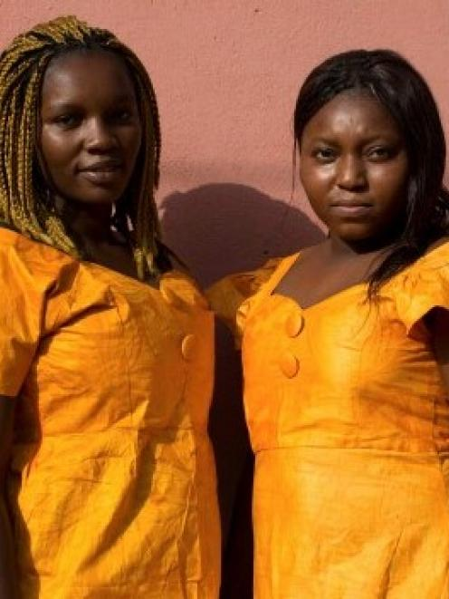 Friends Nhama Mane (L) and Suncar Darame pose in matching outfits in the Mistra district of...