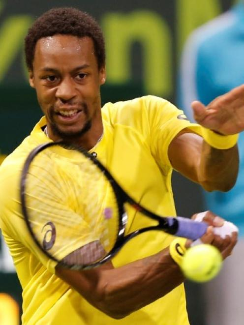 Gael Monfils hits a return against Rafael Nadal during their final match at the Qatar Open....