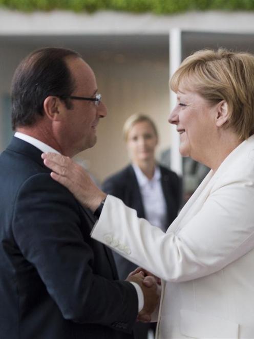 German Chancellor Angela Merkel welcomes France's President Francois Hollande before talks at the...