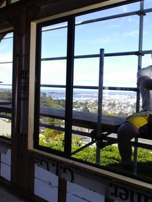 GJ Gardner Homes Otago apprentice builder Jason Bint installs a window at a new house on Pine...