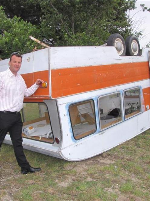 Glen Christiansen, of Cromwell, inspects his family's caravan which was lifted into the air and...