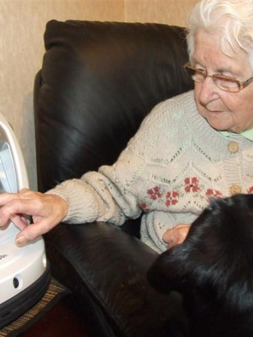 Gore woman Peggy Haar  uses her healthbot 'Sneezy' in her home,  watched by her black labrador,...