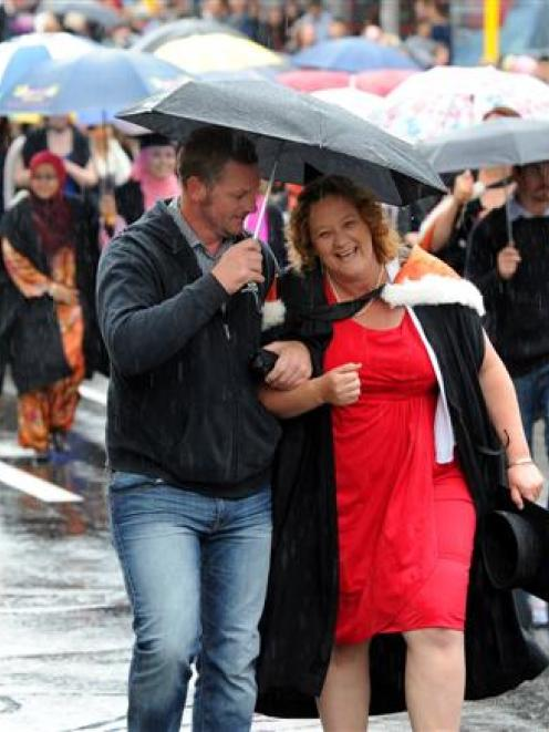 Graduate Jackie Gibson is sheltered under an umbrella by her brother Nigel Rook during a wet...