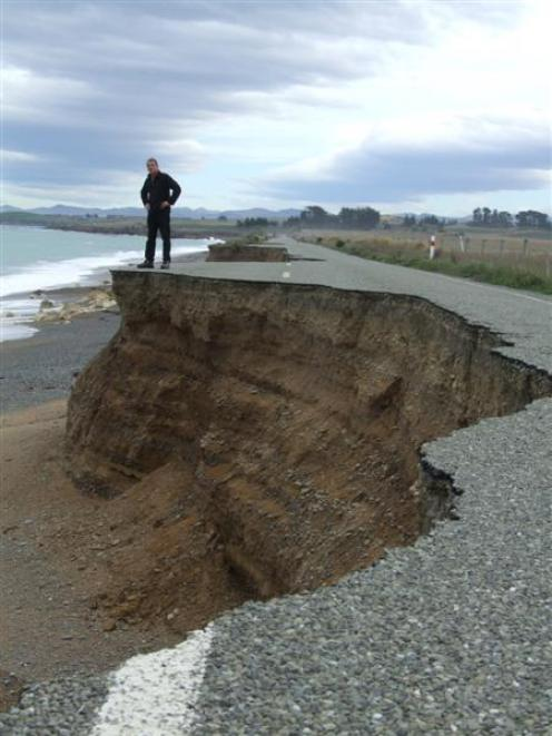Graeme Clark views the effect of coastal erosion on a closed section of Beach Rd, between...