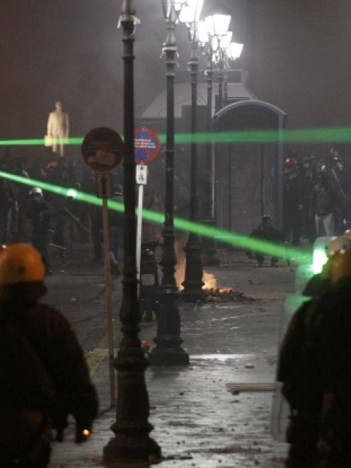 Green laser pointers are aimed at riot police by demonstrators during violent protests in central...