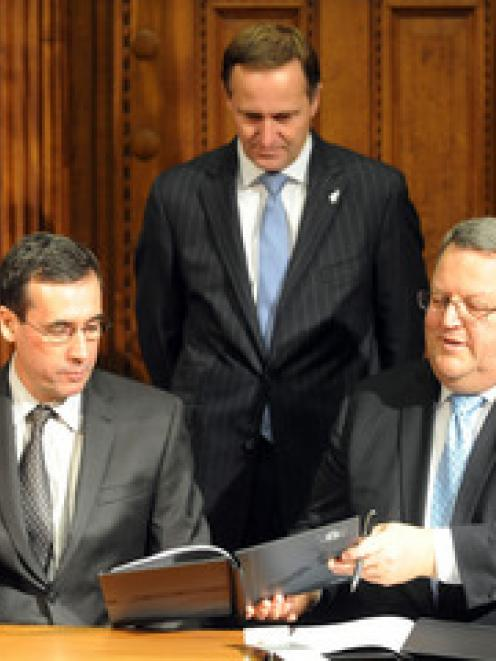 Minister of Energy and Resources Gerry Brownlee, right signs an agreement with Marcelo Carlos...