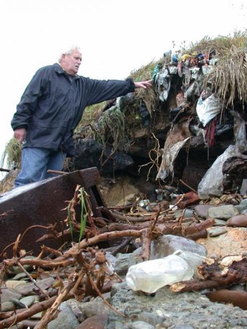 Hampden resident Bent Jansen examines rubbish exposed by coastal erosion of the Hampden dump....
