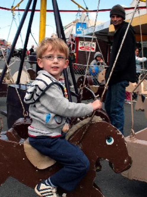 Cameron Marriott (4) enjoys a ride on the merry-go-round at the South Dunedin Street Festival on...
