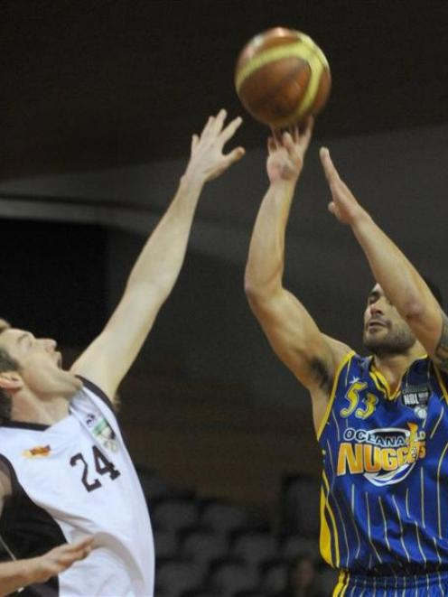 Harbour Heat defender Dillon Boucher tries to block the shot of Otago Nuggets captain Sam To...