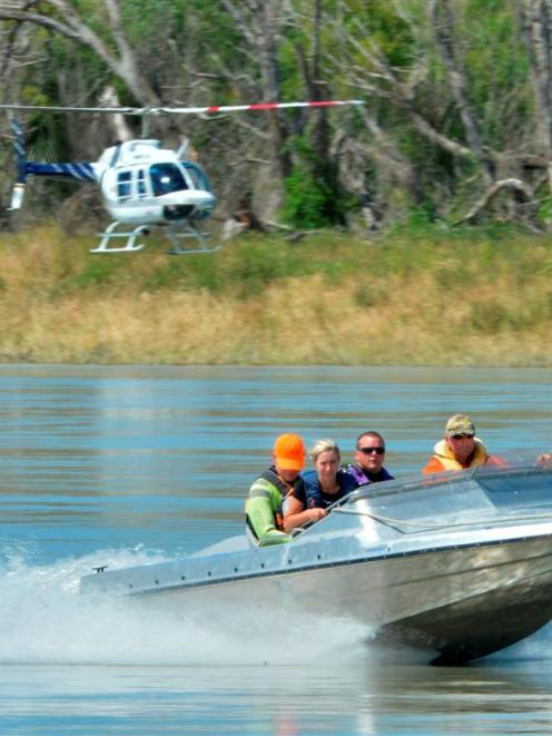 Helicopter and jet-boat-borne search parties head out on the Clutha River yesterday looking for...