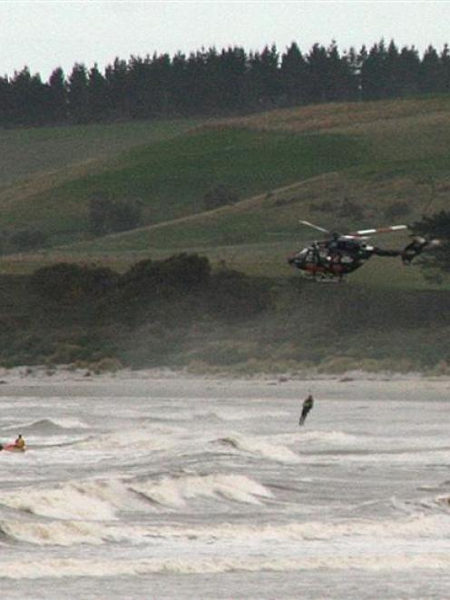 Helicopter rescuer Paul Sharp is attached to the rescued man while Scott Weatherall (left) and...