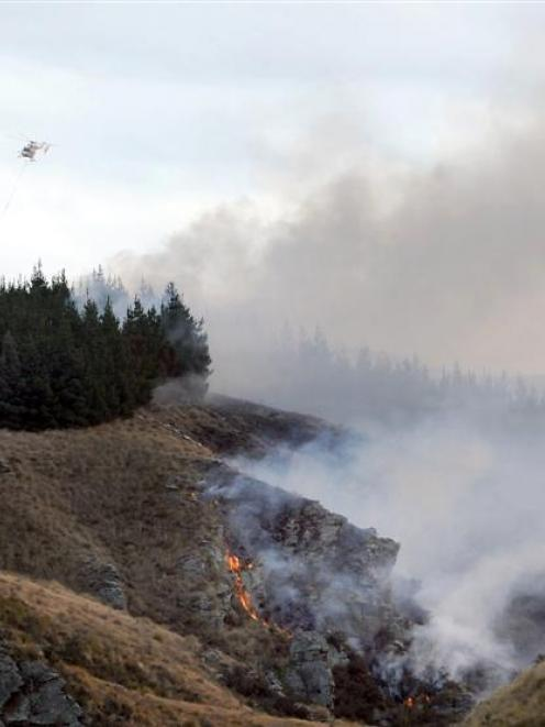 Helicopters with monsoon buckets join the fight to extinguish a scrub fire near Hyde on Saturday....
