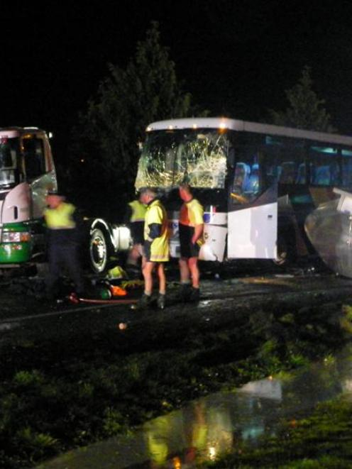 Helpers attend the accident scene after a dairy tanker and bus collided near Mataura last night....