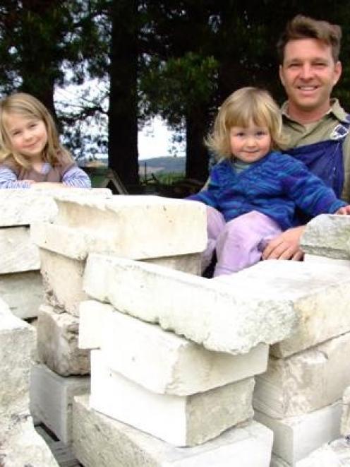 Herbert sculptor Matt King, and his children Matilda (4) and Albert (1), with some of the Oamaru...