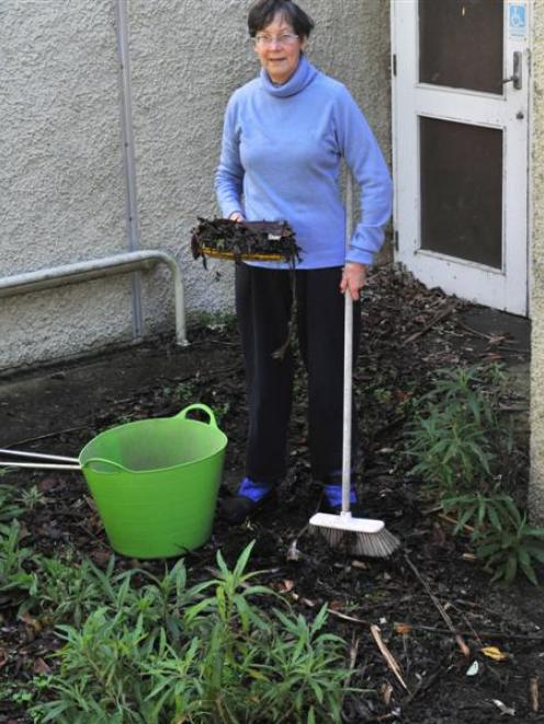 High Street School neighbour Margie Harris clears leaves and weeds from an entrance to the former...