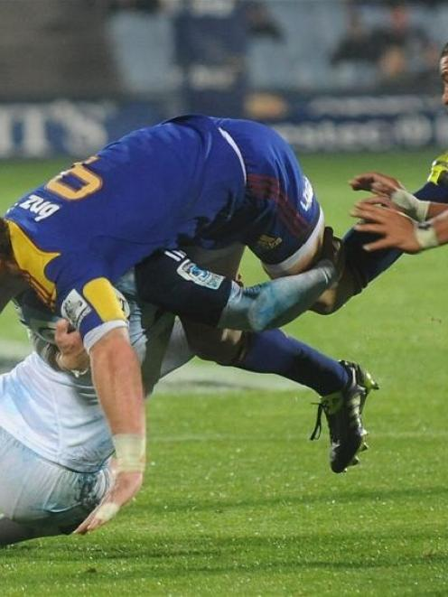 Highlanders halfback  Jimmy Cowan is tackled by a Blues defender (obscured) while Blues hooker...