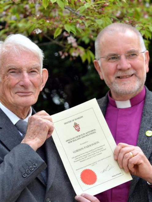 Historian Gordon Parsonson (left) holds a certificate, presented to him by the Anglican Bishop of...