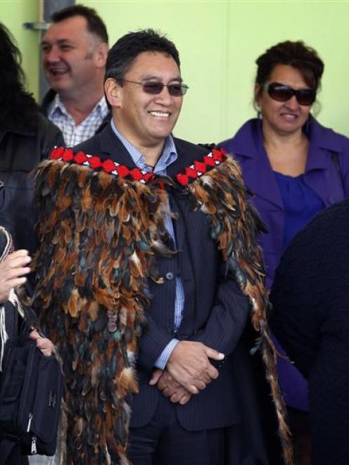 Hone Harawira, dressed in a feather cloak (korowai), is welcomed on to Rawhitiroa kura kaupapa...